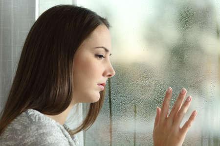 Foto de Sad woman looking the rain falling through a window at home or hotel - Imagen libre de derechos