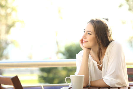 Photo for Pensive happy woman remembering looking at side sitting in a bar or home terrace - Royalty Free Image