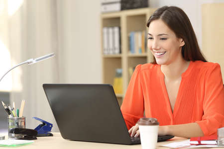 Foto de Beautiful freelancer working with a laptop in a desk at home room or office - Imagen libre de derechos