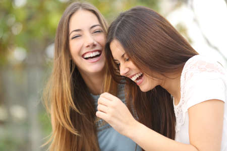 Foto de Two happy woman friends laughing together in a park with a green background - Imagen libre de derechos