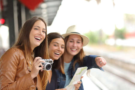 Photo pour Group of three traveler girls traveling and waiting in a train station platform - image libre de droit