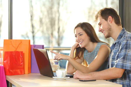 Photo pour Couple of shoppers with shopping bags buying online and choosing products in a coffee shop - image libre de droit