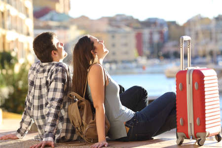 Foto de Side view of a couple of 2 tourists with a suitcase sitting relaxing and enjoying vacations in a colorful promenade. Tourism concept - Imagen libre de derechos