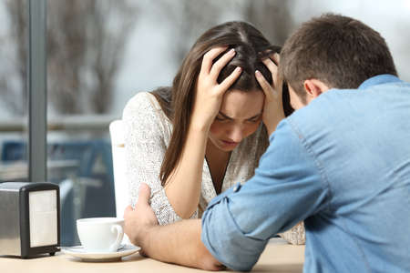 Foto de Male comforting to a sad depressed female who needs help in a coffee shop. Break up or best friend concept - Imagen libre de derechos