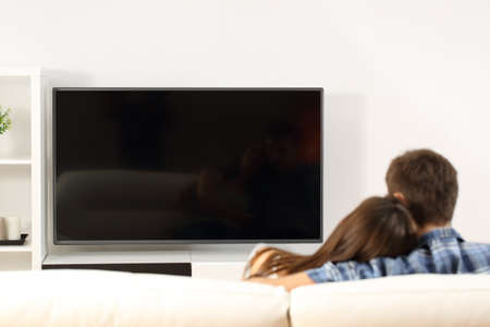 Foto de Back view of a couple watching tv in a couch at home. Blank screen view - Imagen libre de derechos