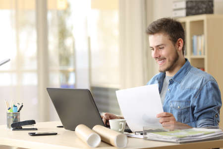 Foto de Entrepreneur working with a laptop and holding a document in a little office or home - Imagen libre de derechos