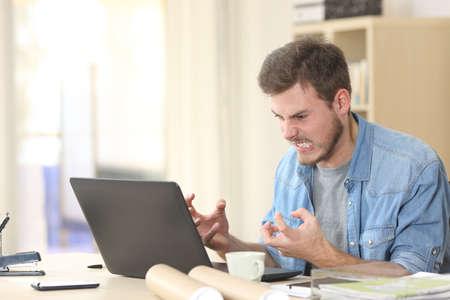 Foto de Entrepreneur angry and furious with a laptop in a little office or home - Imagen libre de derechos