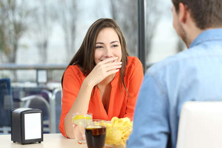 Photo for Woman covering her mouth to hide smile or bad breath during a date in a coffee shop with a window in the background - Royalty Free Image