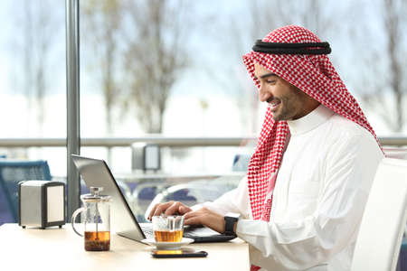 Photo for Arab saudi man working online with a laptop and smartwatch in a coffee shop or an hotel bar with a window and outdoor terrace in the background - Royalty Free Image