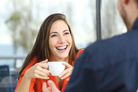 Foto de Happy woman dating in a coffee shop looking at her partner and holding a cup - Imagen libre de derechos