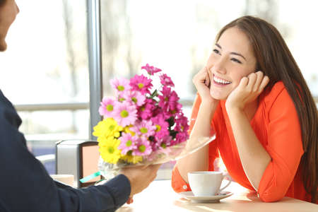 Photo pour Candid woman dating in a coffee shop and looking her boyfriend who gives her a bunch of flowers - image libre de droit