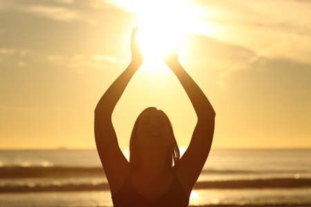 Photo for Front view of a back light of faithful woman silhouette holding sun on the beach at sunrise with a warm background - Royalty Free Image