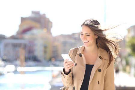 Photo for Happy beautiful woman walking and writing or reading sms messages on line on a smart phone while the wind moves her hair in a street of a port urbanization - Royalty Free Image