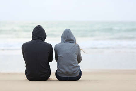Foto de Back view of two sad teenagers sitting on the sand of the beach and looking at horizon in a bad weather day - Imagen libre de derechos