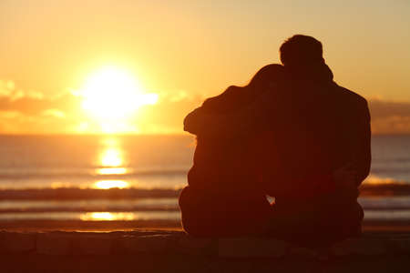 Foto de Back view of a couple silhouette watching sun at sunset on the beach in winter with a warmth light - Imagen libre de derechos