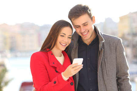 Photo for Couple sharing a smart phone watching media content outdoors in winter - Royalty Free Image