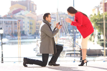 Photo pour Profile of a proposal of a full body of a fashion elegant couple with a man asking marry to his girlfriend in an idyllic port of an urbanization - image libre de droit