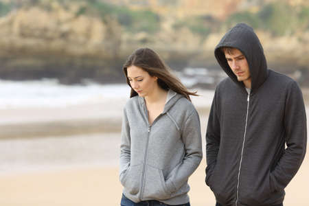 Photo pour Couple of angry and sad teenagers together walking on the beach - image libre de droit
