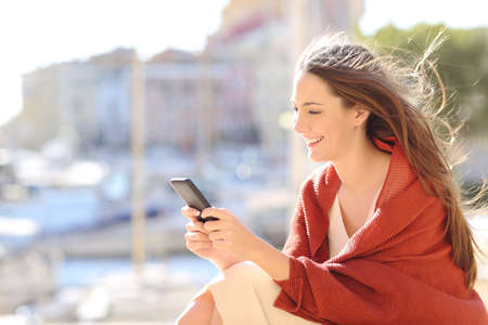 Foto de Girl sitting using a smart phone texting messages on line in a port of urbanization with the sea in the background and the wind moving her hair - Imagen libre de derechos