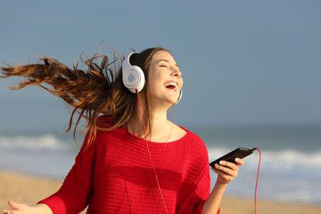 Foto de Happy girl wearing red colorful jersey dancing singing and listening music on line with headphones from a smart phone on the beach - Imagen libre de derechos