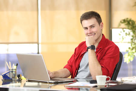 Photo for Entrepreneur working at office sitting in a desktop and looking at you - Royalty Free Image