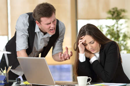 Photo pour Bullying with an out of control boss shouting to a stressed employee in a desktop at office interior - image libre de droit