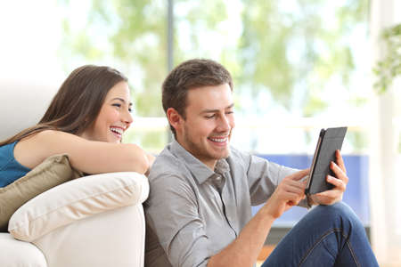 Photo for Cheerful couple using a tablet on line sitting in the living room at home with a window in the background - Royalty Free Image