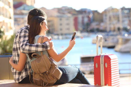 Foto de Couple of tourists sitting searching information or booking an hotel on a smart phone on vacations - Imagen libre de derechos