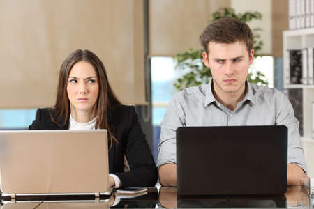 Foto de Front view of two angry businesspeople using computers disputing at workplace and looking sideways each other with envy - Imagen libre de derechos