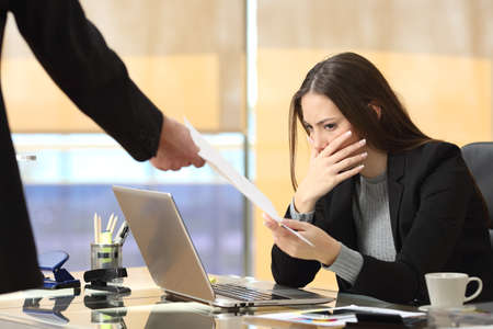 Photo for Worried businesswoman receiving a notification from a colleague in her workplace at office - Royalty Free Image