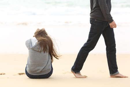 Foto de Teenager couple breaking up and ending relation after argument. Boyfriend legs leaves his sad girlfriend and go away - Imagen libre de derechos