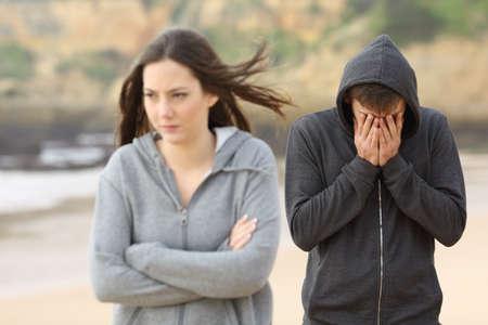 Foto de Teenager couple breaking up after argument. The angry girlfriend is rejecting her sad boyfriend - Imagen libre de derechos