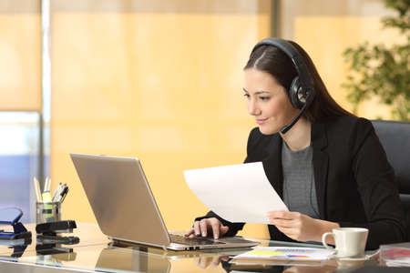 Photo pour Freelance operator working online with a laptop and headsets and holding a document at office - image libre de droit
