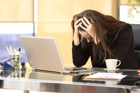 Foto de Desperate businesswoman on line worried after bankruptcy in front of a laptop with her hands in the head at office - Imagen libre de derechos