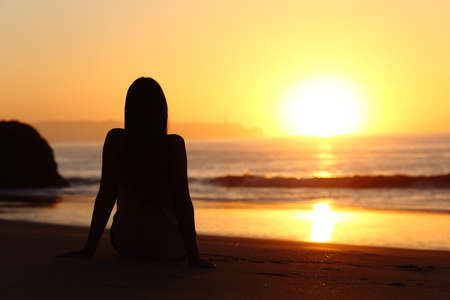 Foto de Back view of a woman silhouette sitting on the sand of a beach watching sun at sunrise with the horizon and ocean in the background - Imagen libre de derechos