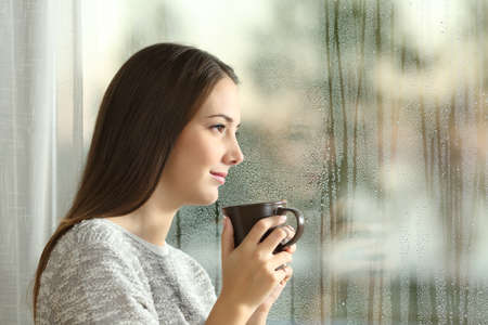 Photo pour Side view portrait of a pensive woman looking away through a wet window in a rainy day at home - image libre de droit