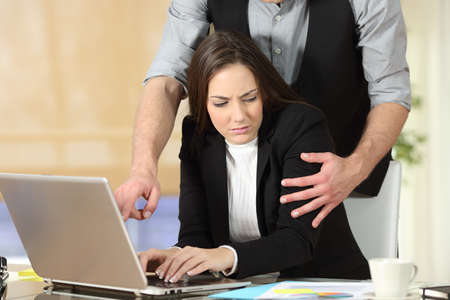Photo pour Harassment with a boss touching the arm to his secretary who is sitting in his workplace at office - image libre de droit
