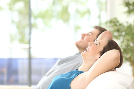 Photo pour Side view of a happy couple breathing and resting lying in a couch at home with a window in the background - image libre de droit