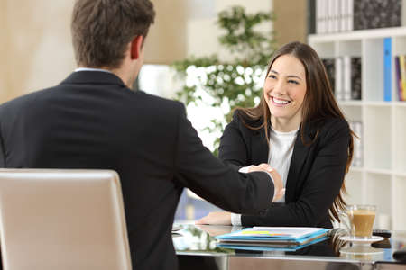 Photo pour Businesspeople handshaking after negotiation or interview at office - image libre de droit