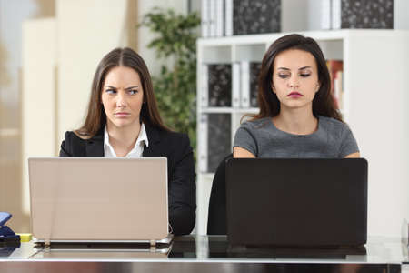Foto de Front view of two angry businesswomen looking each other with hate working with laptops at office - Imagen libre de derechos