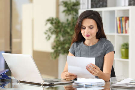 Photo for Portrait of a businesswoman working at office reading a letter in a desktop - Royalty Free Image