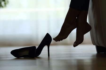 Photo for Back light silhouette of a woman feet resting at home with shoes on the floor - Royalty Free Image