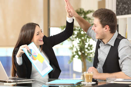 Foto de Successful coworker showing a growth graph celebrating good results and giving high five in an office interior - Imagen libre de derechos