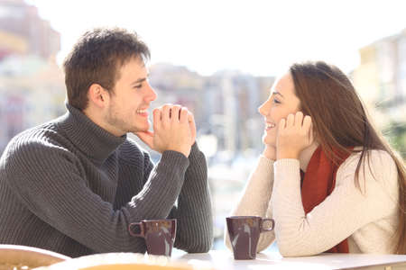 Photo pour Side view of a happy couple dating and flirting in love looking each other in a bar terrace with a port of urbanization in the background - image libre de droit
