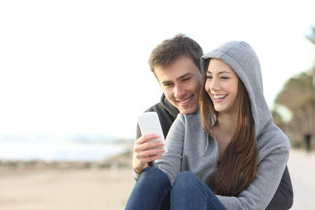 Photo pour Portrait of couple of teenagers watching media content in a smart phone outdoors in the beach - image libre de droit