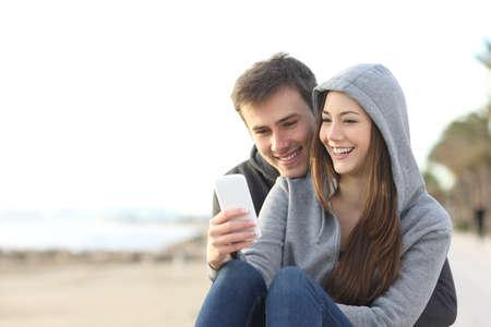 Foto de Portrait of couple of teenagers watching media content in a smart phone outdoors in the beach - Imagen libre de derechos