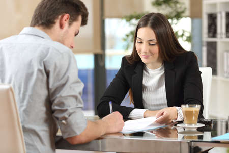 Photo pour Client signing a document in an office with a businesswoman looking the contract - image libre de droit