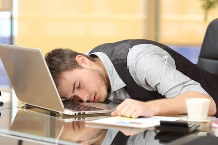 Foto de Tired overworked businessman sleeping over a laptop in a desk at job in his office - Imagen libre de derechos