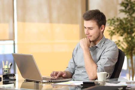 Foto de Attentive entrepreneur working on line browsing a laptop sitting in a desk at office - Imagen libre de derechos