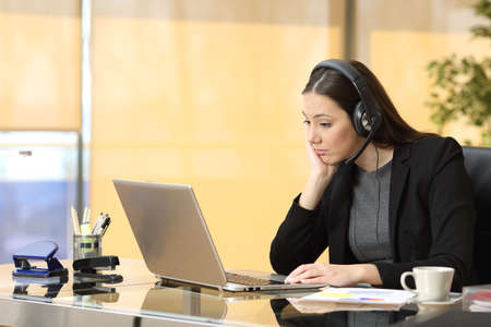 Photo pour Bored operator working on line watching a laptop and listening a conversation with headset at office - image libre de droit